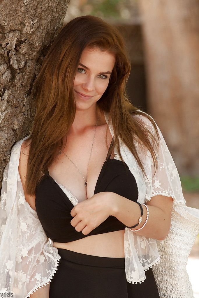 Beautiful dark hair youthful Essie Halladay posing and flashing outside