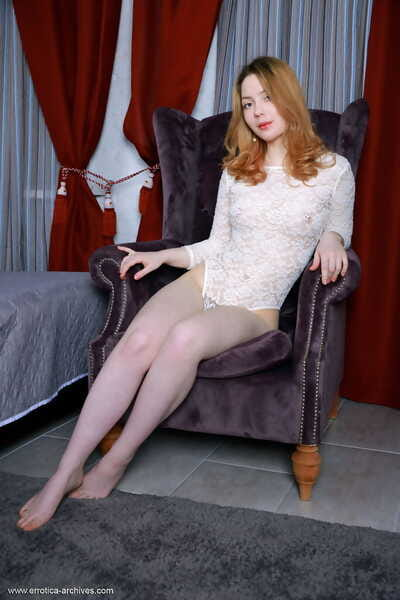Common redhead slithers off her onesie to sample undressed on a velvet chair