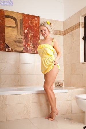 Seductive blondie undressing and rubbing her soapy body in the bathtube