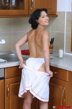 Smiley brunette cheerleader undressing and exposing her goods in the kitchen