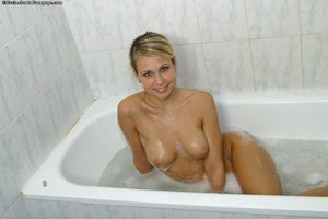 Juvenile blonde Renata wets her enormous boobs in washroom and positions uncovered