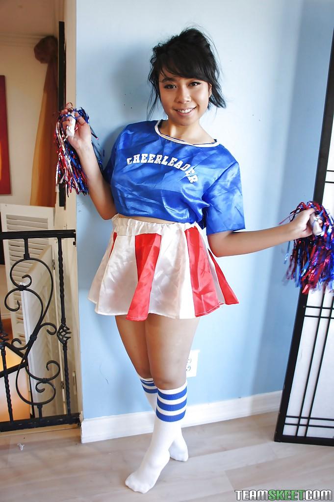 Petite Oriental cheerleader May Lee flashing black panties under skirt