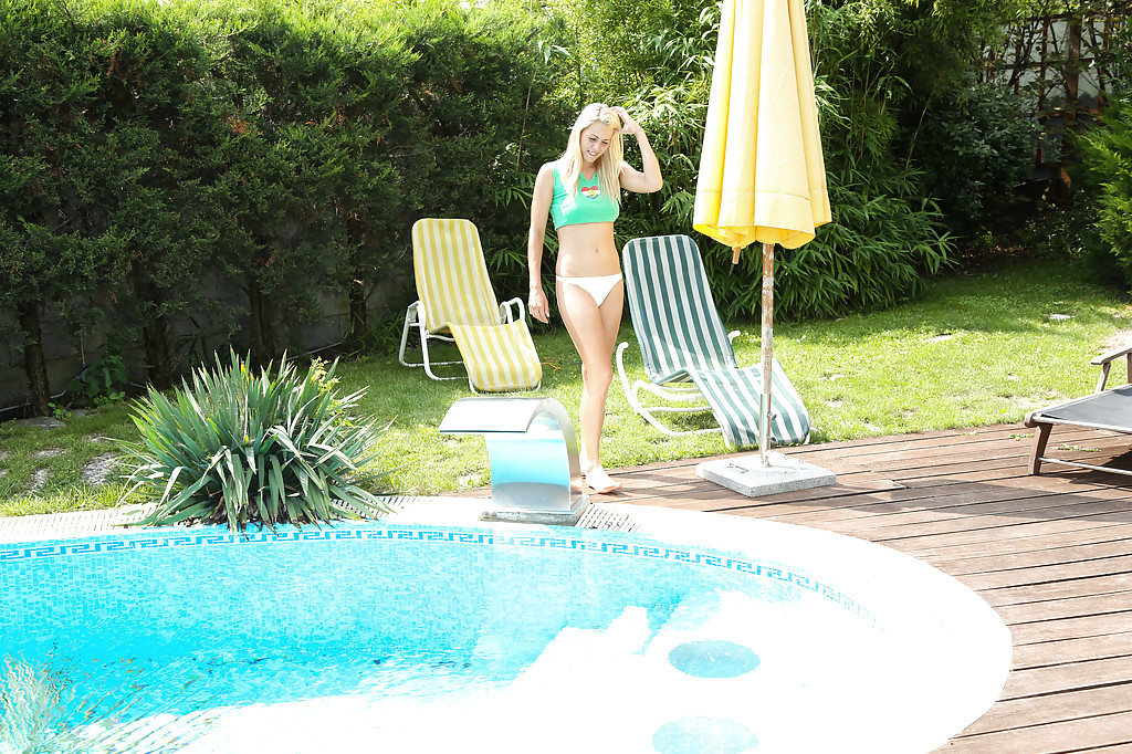 Leggy blonde Christen is sitting at the poolside and playing with puss