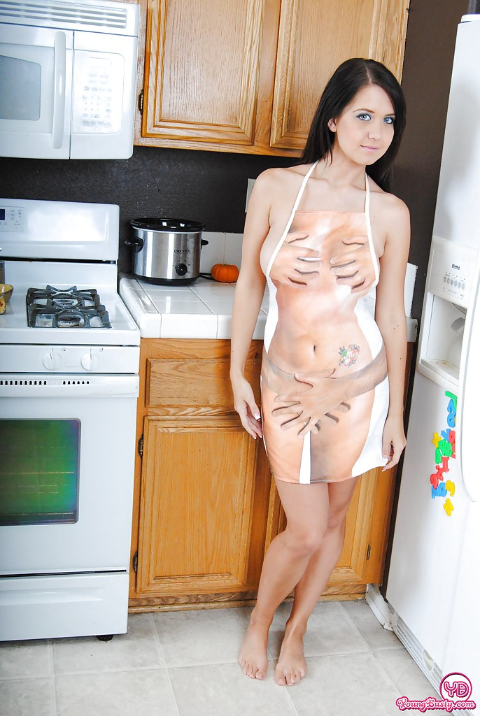 Young and busty brunette beauty showing off pink twat in kitchen