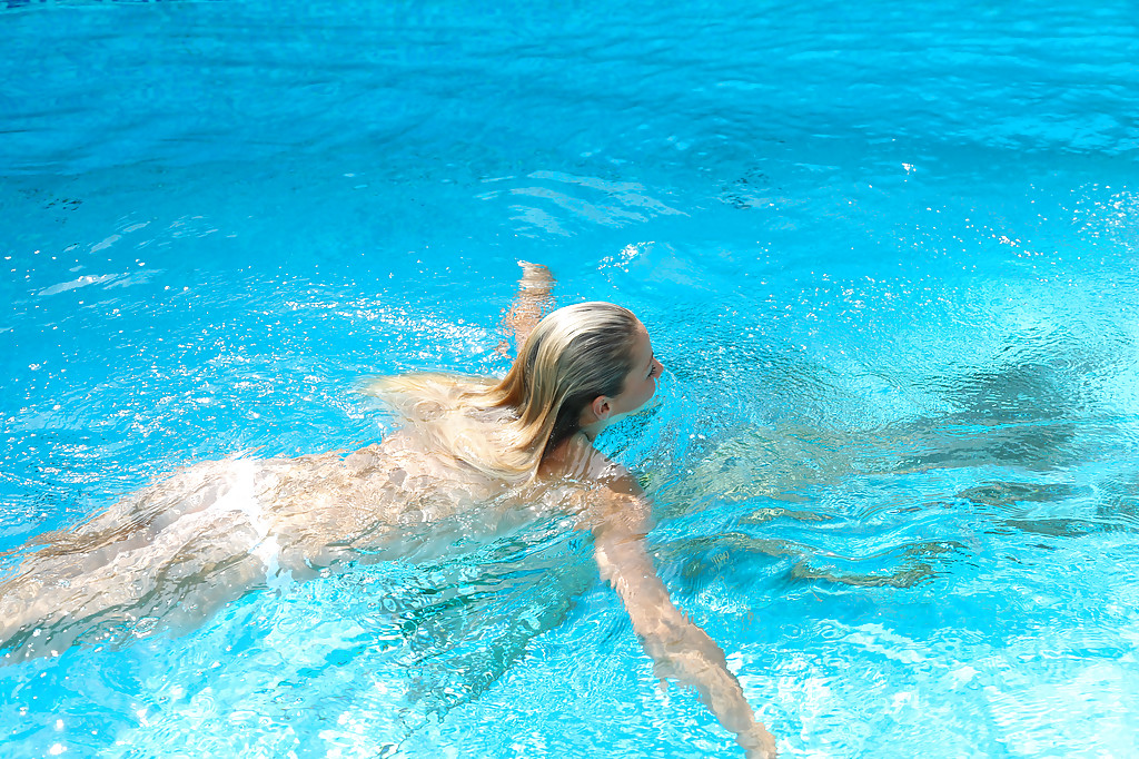 Young blonde Christen is swimming in the pool naked and masturbating