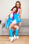 Lovely teen cheerleaders in knee socks have some lesbian fun on a sofa