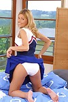 Smiley cheerleader undressing and exposing her slit in close up