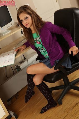 Fascinating young in knee socks undressing and stretching her legs at her workplace